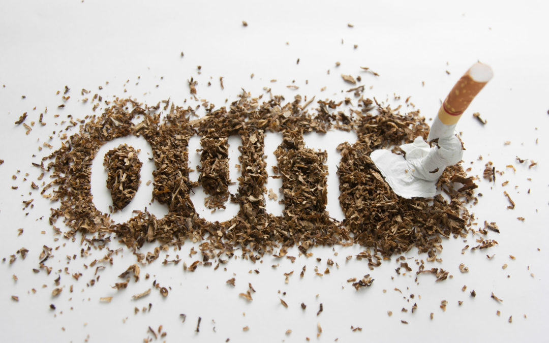 Quit made out of ashes with a cigarette broken next to the word on a white background