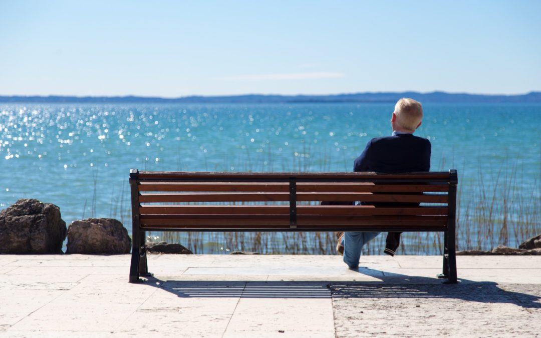 Man sitting alone on a bench watching the ocean
