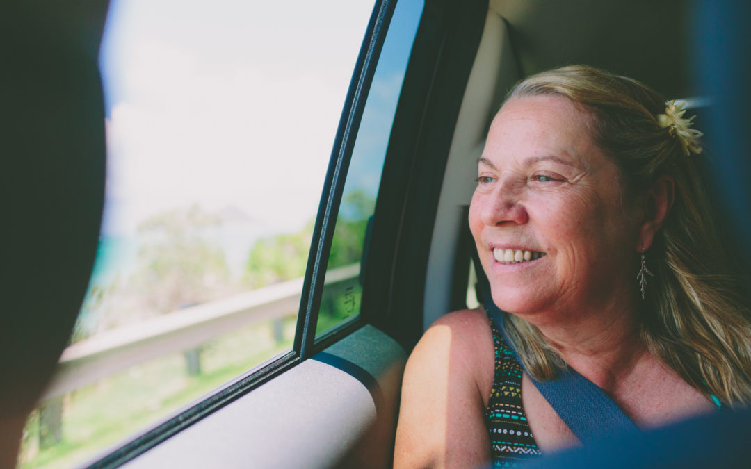 Woman riding in back of car smiling