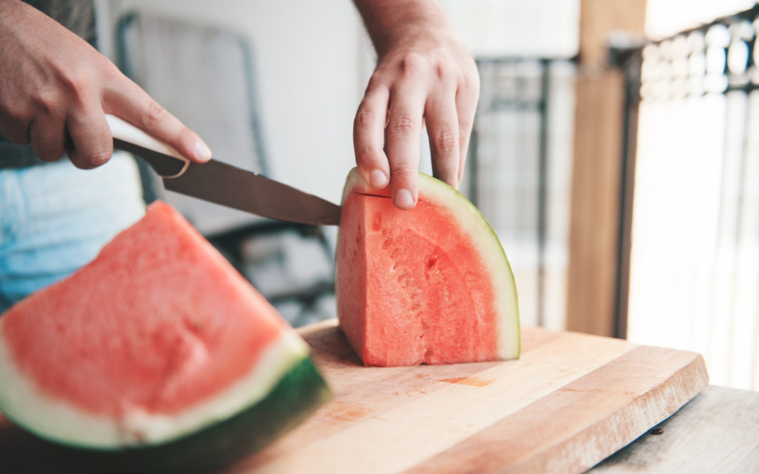 Man cutting up watermelon on a wood cutting board