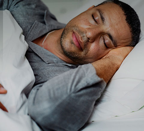 African American man sleeping in bed wearing grey pajamas