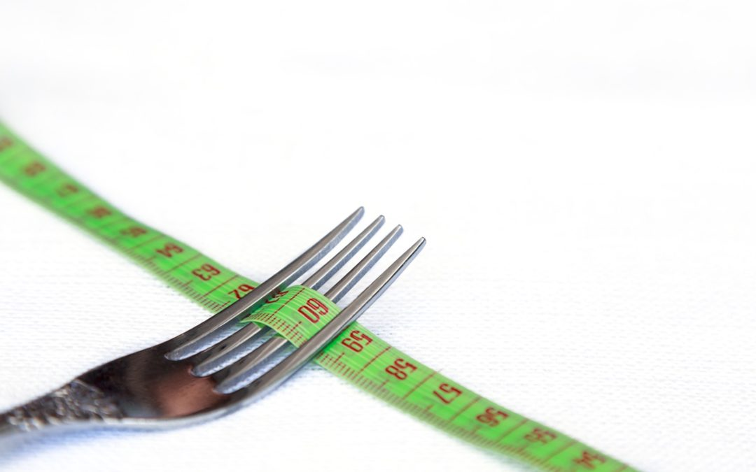 Silver fork with a green tape measure running through it