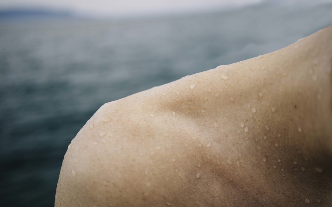 Shoulder of a man with the lake behind him